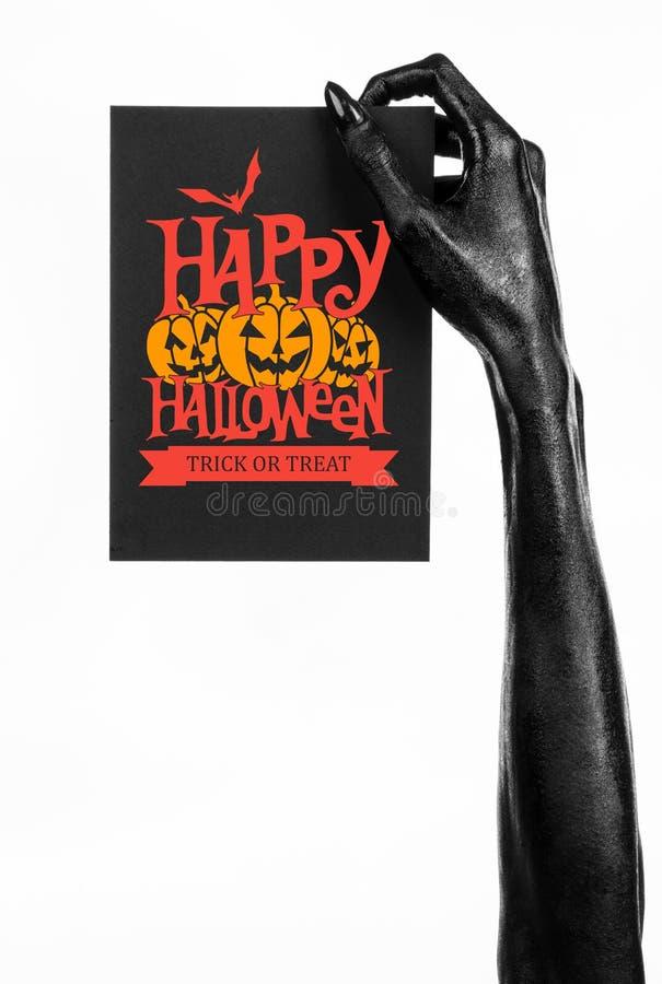 Vykort och lyckligt allhelgonaaftontema: den svarta handen av död som rymmer ett pappers- kort med den lyckliga allhelgonaaftonen royaltyfri bild