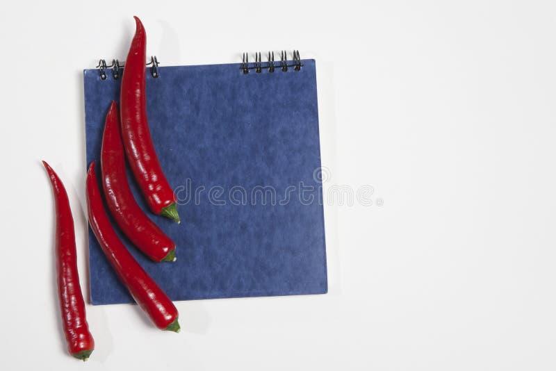 Vykorten för recept blå sketchpad och glödhet peppar som en ram på en vit bakgrund fotografering för bildbyråer
