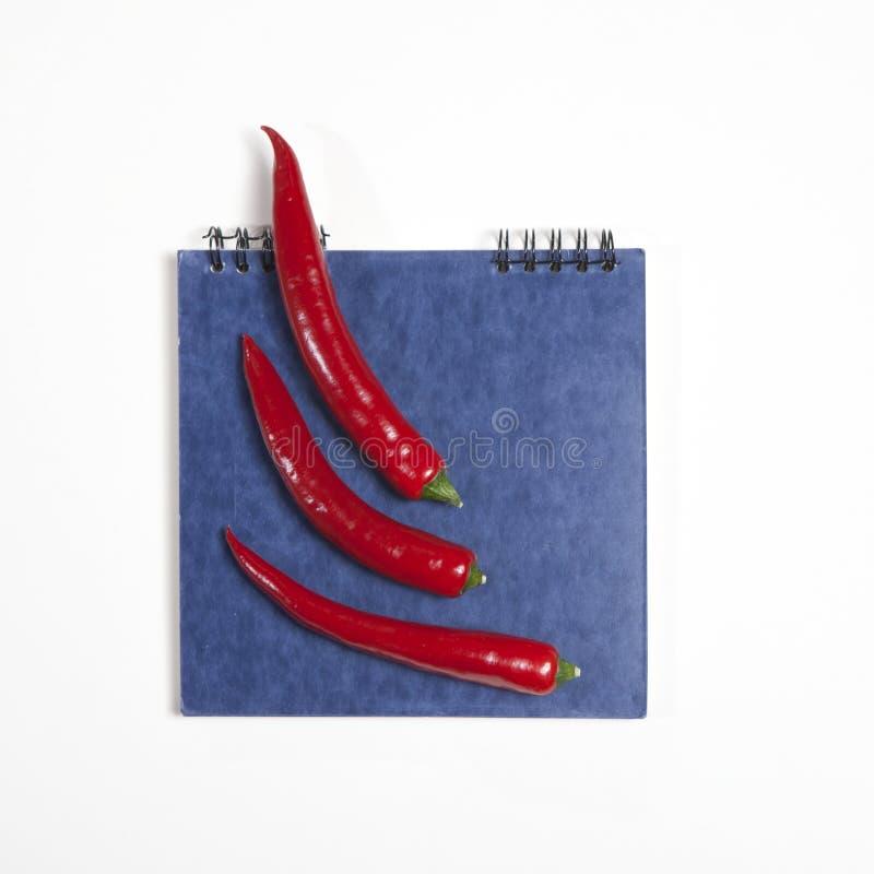 Vykorten för recept blå sketchpad och glödhet peppar som en ram på en vit bakgrund arkivbilder