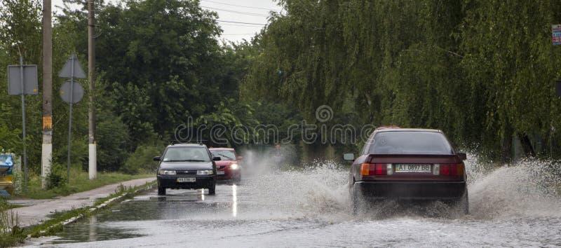 Vyshenky 6月21日,乌克兰 阵雨的后果 汽车通过一个大水坑飞溅在一条被充斥的街道 库存照片