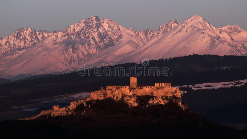 Vysoke Tatry mountain range with Spissky hrad , Slovakia. View of castle ruins of Spissky hrad with Vysoke Tatry mountain range in the background. Castle is stock photography