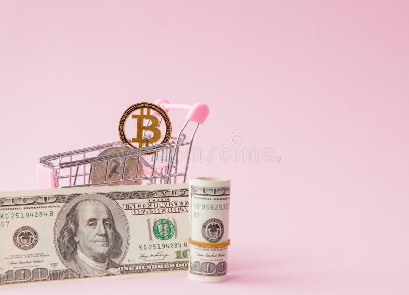 Wózek na zakupy z bitcoin monetą i dolary na różowym tle z kopii przestrzenią fotografia stock