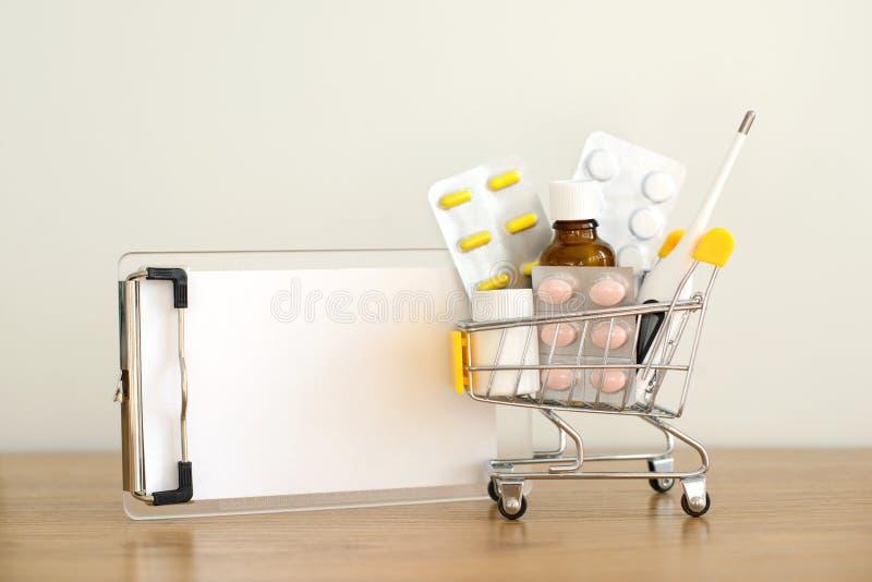 Wózek na zakupy zabawka z medicaments i papier notatką: pigułki, bąbel paczki, medyczne butelki, termometr i przepisu set, obrazy stock