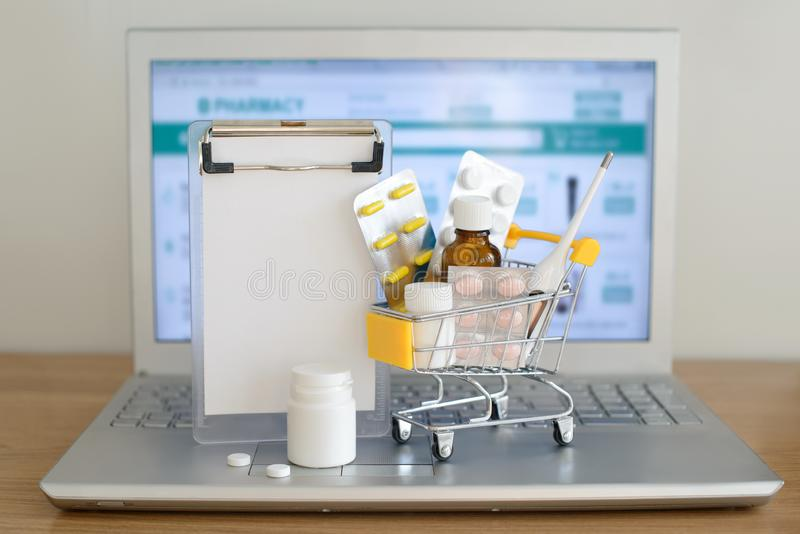 Wózek na zakupy zabawka z medicaments i papier notatka przed laptopu ekranem z apteki stroną internetową na nim zdjęcie royalty free