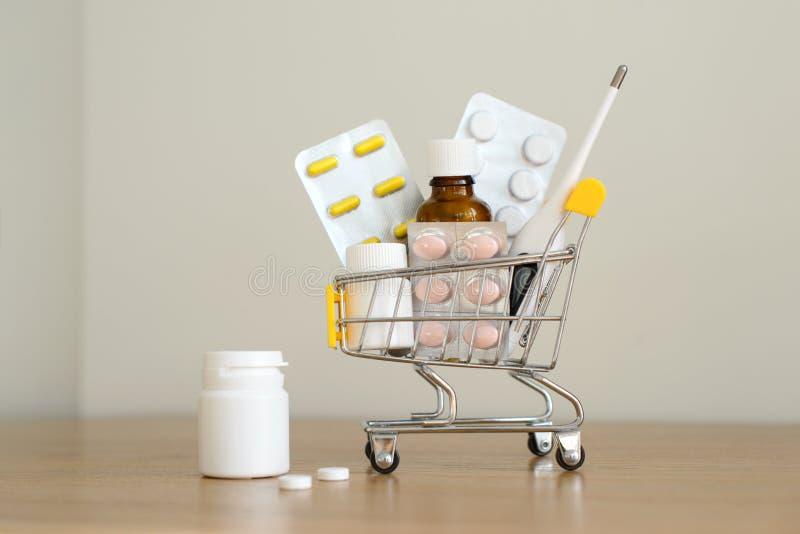 Wózek na zakupy zabawka z medicaments: pigułki, bąbel paczki, medyczne butelki, termometru set Opieki zdrowotnej i medycyny pojęc obrazy royalty free