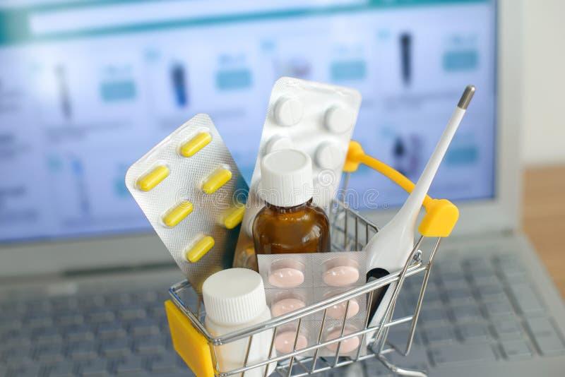 Wózek na zakupy zabawka z medicaments przed laptopu ekranem z apteki stroną internetową na nim Pigułki, bąbel paczki, medyczne bu fotografia stock