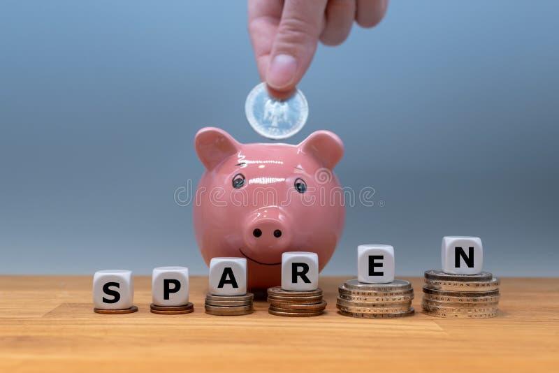Würfel bilden das deutsche Wort 'sparen ''sparen Geld 'auf englisch lizenzfreie stockbilder