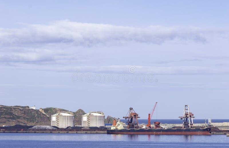 Węglowy ładunku statek cumujący w porcie z podnośnymi ładunków żurawiami, statkami i adrą, zdjęcie royalty free