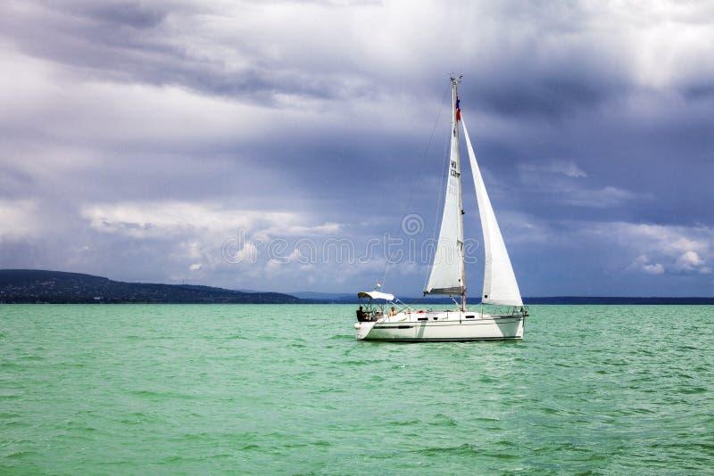 Węgry, Jeziorny Balaton, 06/03/2016 Żeglowanie jacht w morzu z turkus wodą Ponury niebo przed deszczem fotografia stock