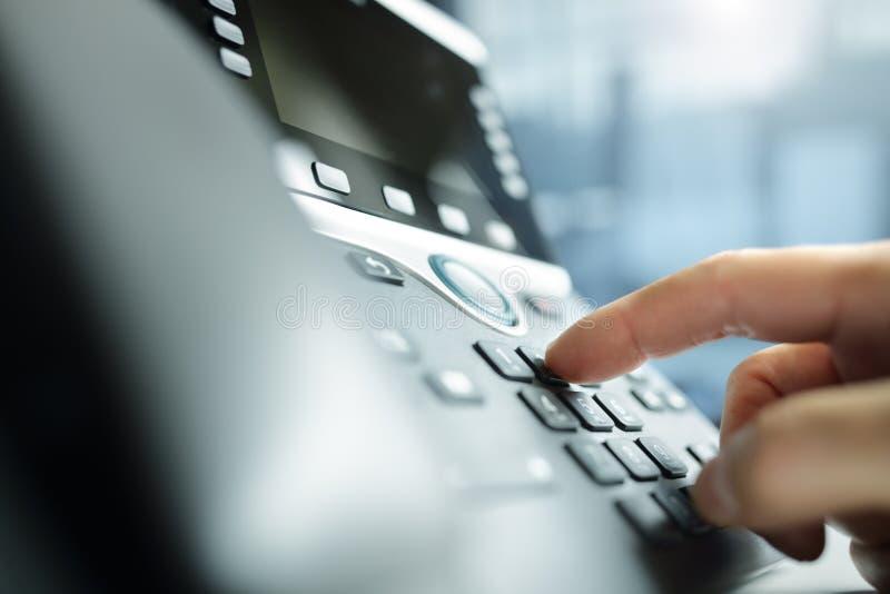 Wählen eines Telefons im Büro stockbilder