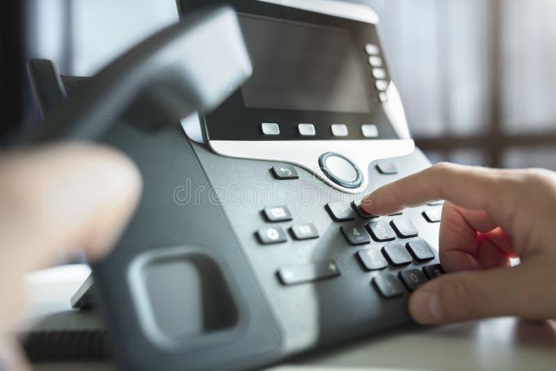 Wählen eines Telefons im Büro stockbild