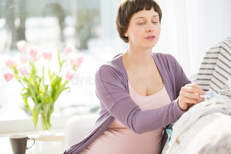 Wählen von Babykleidung lizenzfreie stockbilder