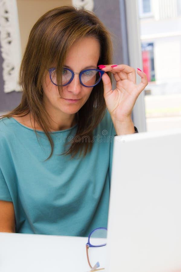 Wählende und kaufende Brillen der Brunette Frau im Optikersalon oder -geschäft lizenzfreie stockfotos