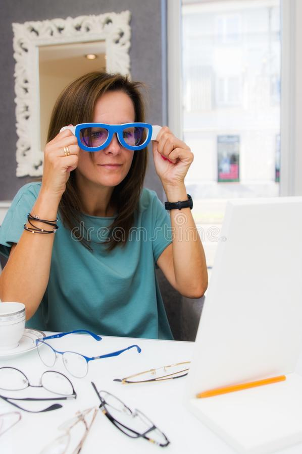 Wählende und kaufende Brillen der Brunette Frau im Optikersalon oder -geschäft lizenzfreie stockfotografie