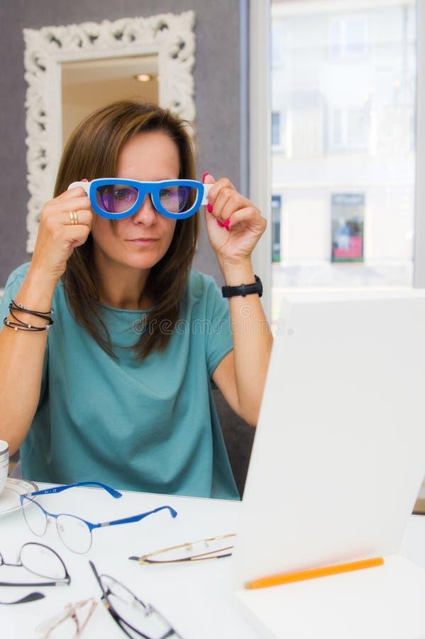 Wählende und kaufende Brillen der Brunette Frau im Optikersalon oder -geschäft lizenzfreie stockbilder
