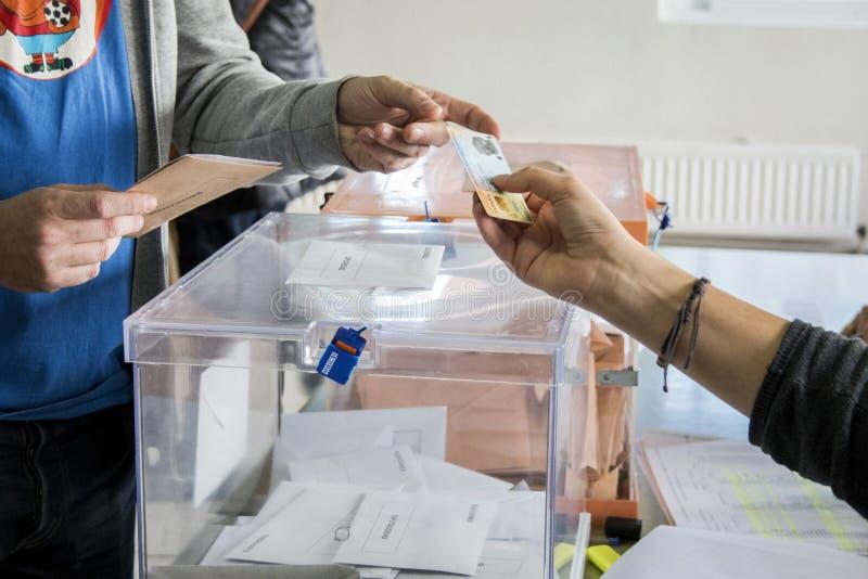 Wähler, der seinen Personalausweis nahe bei Wahlurnen am spanischen Parlamentswahltag in Madrid, Spanien zeigt lizenzfreies stockbild