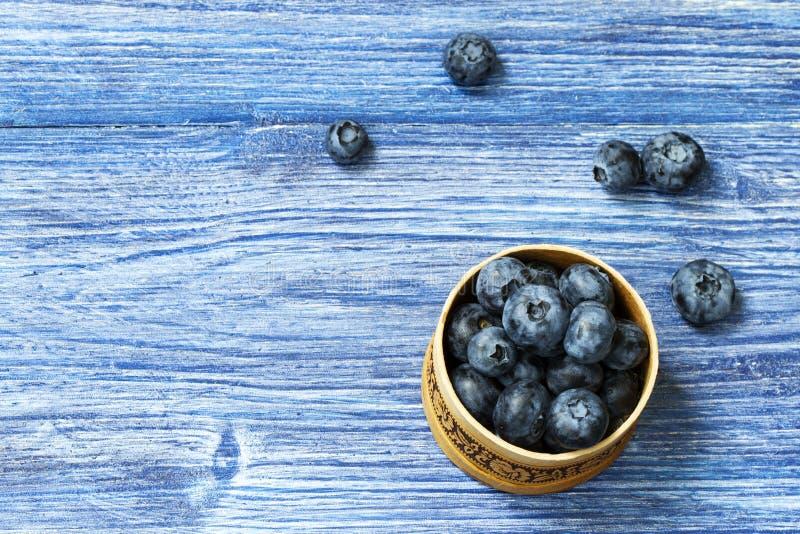 Wählte frisch die saftigen und frischen Blaubeeren in einer russischen Suppengrünbarkenschüssel auf rustikaler Weinlesetabelle au stockbild
