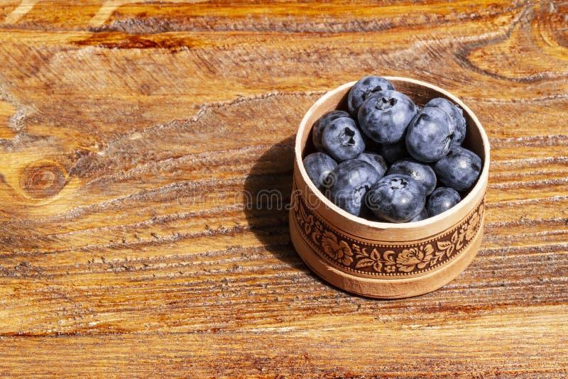 Wählte frisch die saftigen und frischen Blaubeeren in einer russischen Suppengrünbarkenschüssel auf rustikaler Weinlesetabelle au lizenzfreies stockfoto