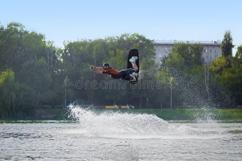Während wakeboarding Mann, der über die Wellen springt stockbilder