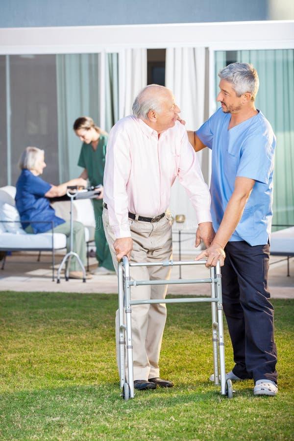 Wärter, der älteren Mann bei der Unterstützung tröstet lizenzfreie stockfotografie