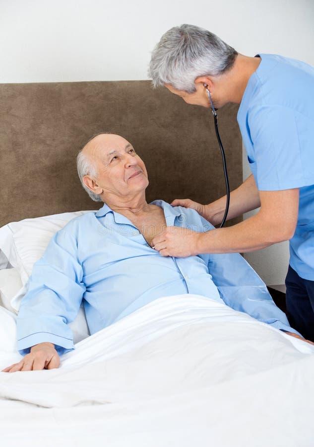 Wärter, der älteren Mann mit Stethoskop überprüft stockfotos