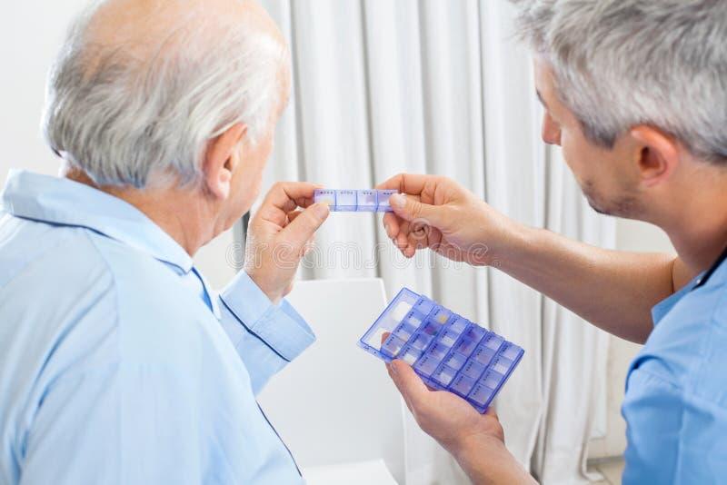 Wärter, der dem Senior Verordnungs-Medizin zeigt lizenzfreies stockfoto
