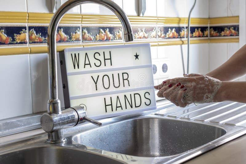 Wäsche die Hände mit einem Meldungskasten hinter dem, wo es heißt, wasche deine Hände während der Quarantäne lizenzfreie stockfotografie