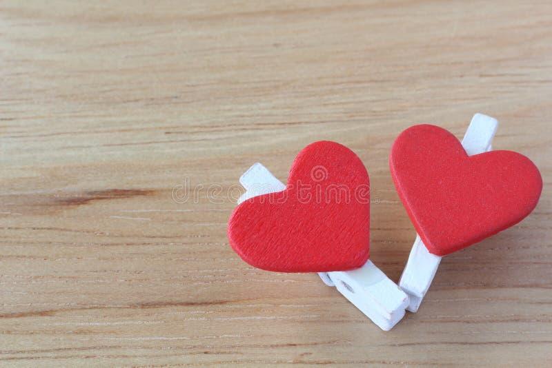 Wäscheklammer zwei und rote Herzen auf dem hölzernen Brett lizenzfreies stockfoto