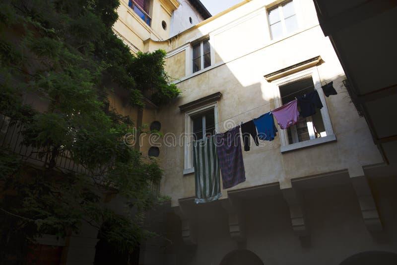 Wäscherei, die in einem italienischen Hof im heißen Sommerlicht hängt stockbild