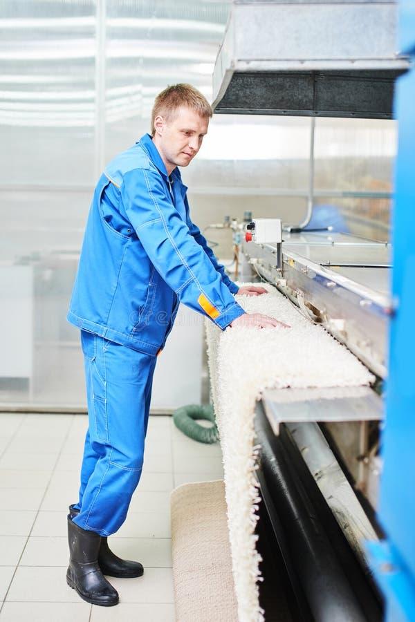 Wäschereiarbeitskraft bei dem Arbeiten an dem Automaten für das Trocknen von Teppichen stockfotos