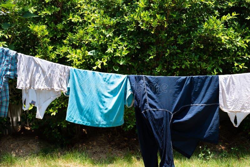 Wäschereistoff, der am Wäscheleine Baumhintergrund hängt stockbild