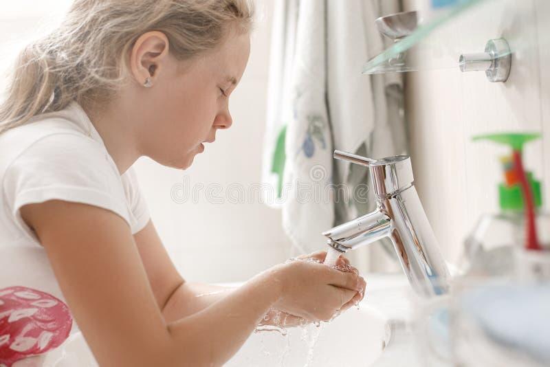 wäscht jähriges Mädchen 8 ihr Gesicht im Badezimmer morgens lizenzfreies stockbild