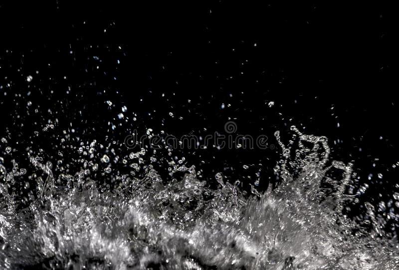 Wässern Sie das Spritzen, das auf schwarzem Hintergrund mit Kopienraum, Tropfendetail des funkelnden Wassers transparent ist Plit stockfotos