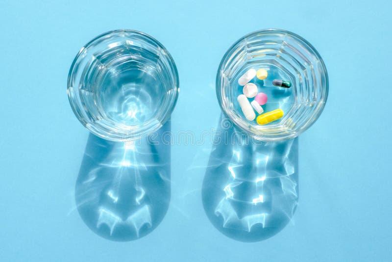 Wässern Sie in der Glasschale und in einer Dosis von Tabletten in einem anderen Glas auf einer blauen Oberfläche lizenzfreies stockbild