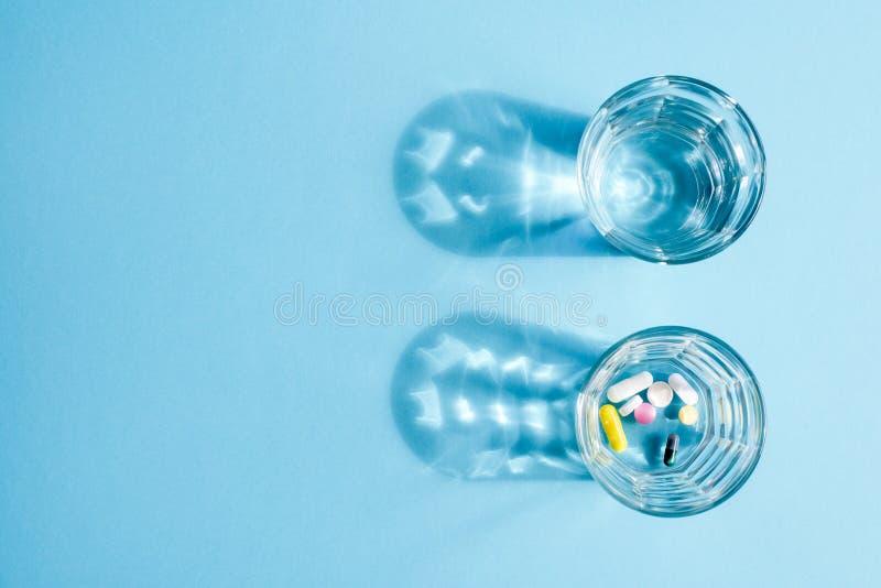 Wässern Sie in der Glasschale und in einer Dosis von Tabletten in einem anderen Glas auf einer blauen Oberfläche stockfoto