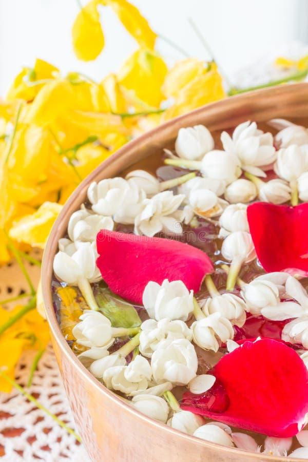 Wässern Sie in der Schüssel, die mit Parfüm und Blumen gemischt wird stockbild