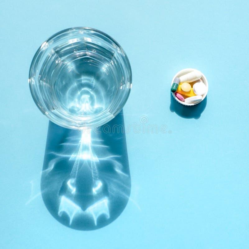 Wässern Sie in einer transparenten Glasschale und in einer Dosis von Tabletten im Deckel auf einer blauen Oberfläche lizenzfreies stockfoto