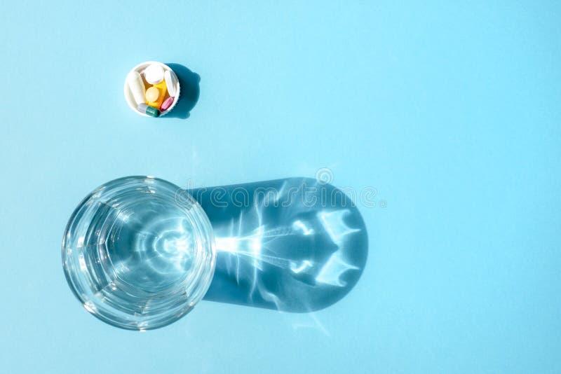 Wässern Sie in einer transparenten Glasschale und in einer Dosis von Tabletten im Deckel auf einer blauen Oberfläche stockbilder