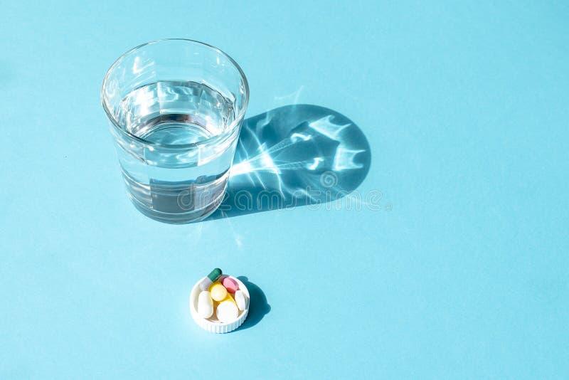 Wässern Sie in einer transparenten Glasschale und in einer Dosis von Tabletten im Deckel auf einer blauen Oberfläche stockbild