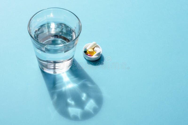 Wässern Sie in einer transparenten Glasschale und in einer Dosis von Tabletten im Deckel auf einer blauen Oberfläche stockfotos