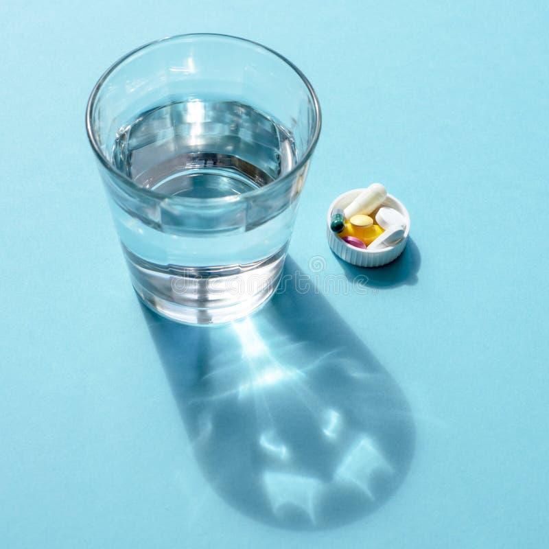 Wässern Sie in einer transparenten Glasschale und in einer Dosis von Tabletten im Deckel auf einer blauen Oberfläche lizenzfreie stockfotografie