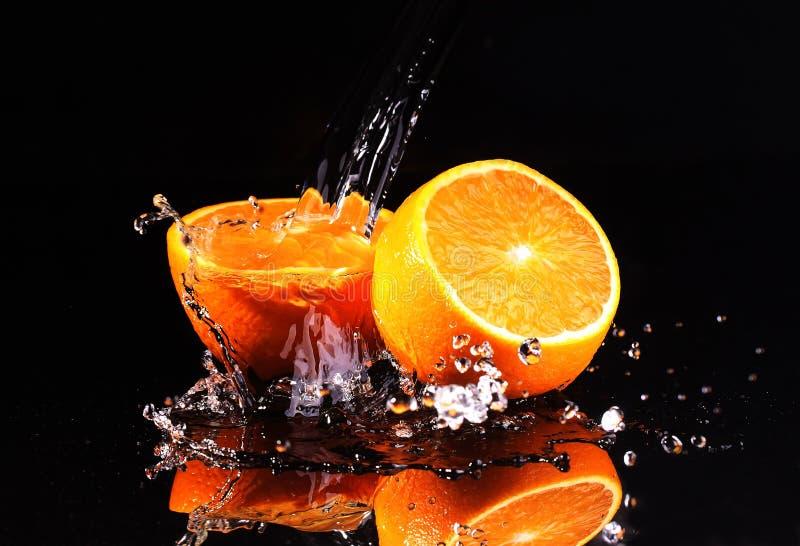 Wässern Sie Flüsse eines Stromes auf orange Hälften, Dynamik einer Flüssigkeit lizenzfreies stockfoto