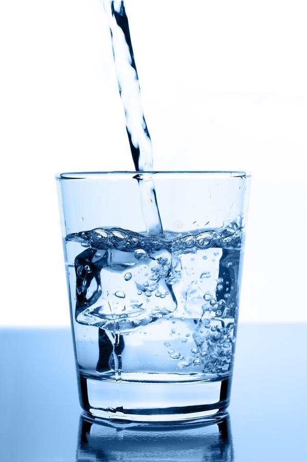Wässern Sie innen gießen zum Glas mit Eiswürfeln stockfotografie