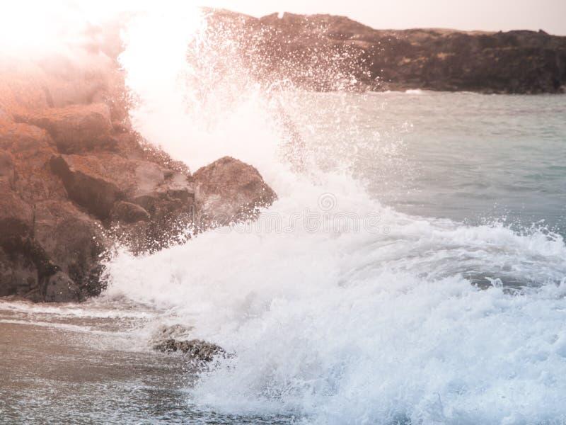 Wässern Sie Spritzen der brechenden Welle auf dem felsigen Ufer lizenzfreie stockfotos