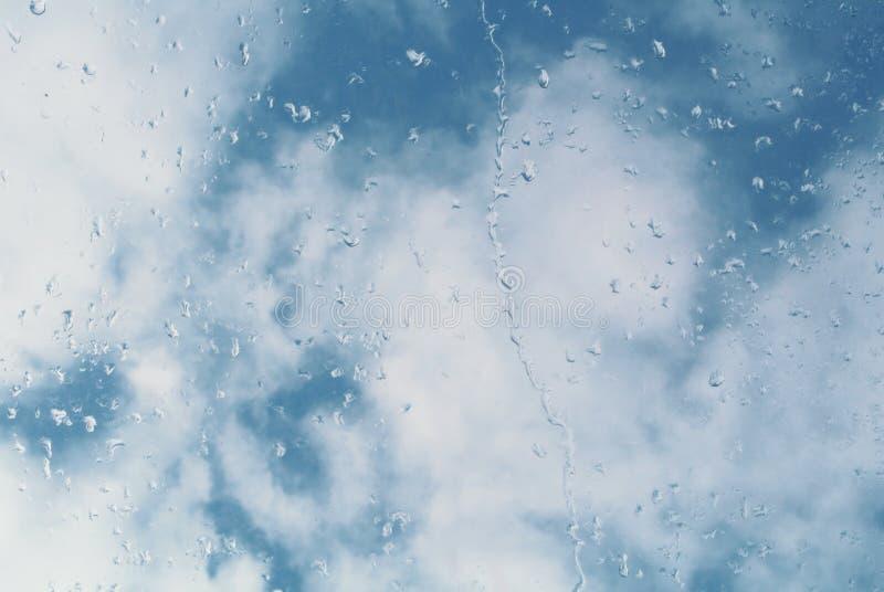 Wässern Sie Tropfen auf einem Fensterglas, ein blauer bewölkter Himmel am backgrou stockbilder