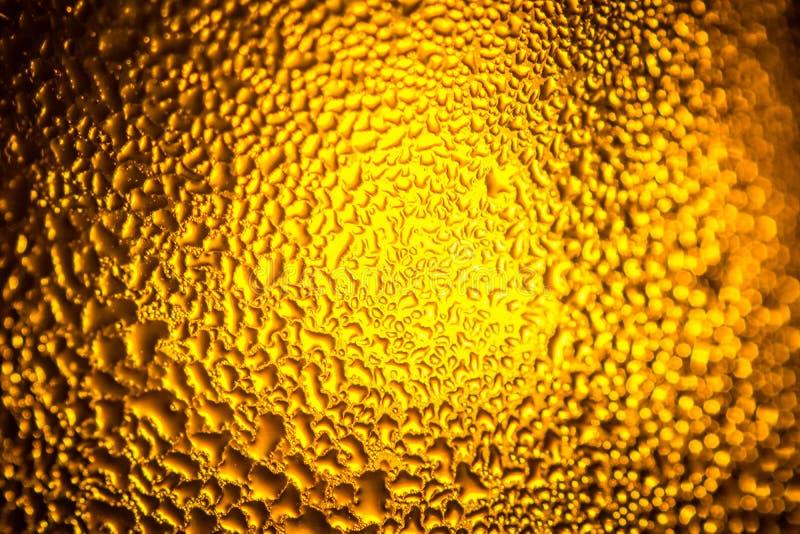 wässern Sie Tropfen auf gelbem Hintergrund mit Scheinwerfermitte stockfoto