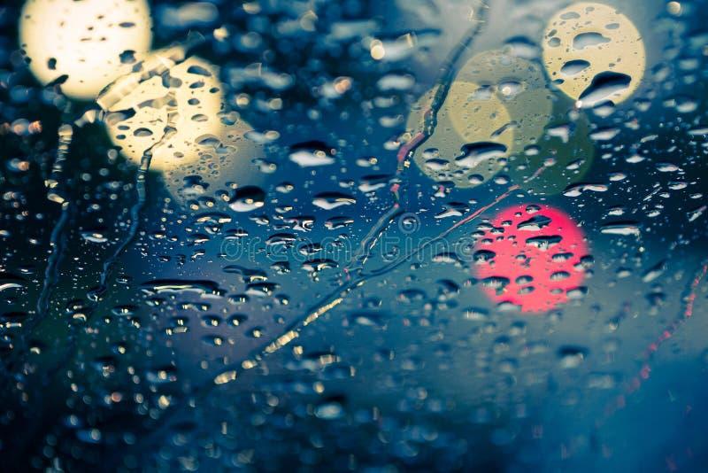 Wässern Sie Tropfen auf vorderem Autogras mit hellem bokeh lizenzfreies stockbild