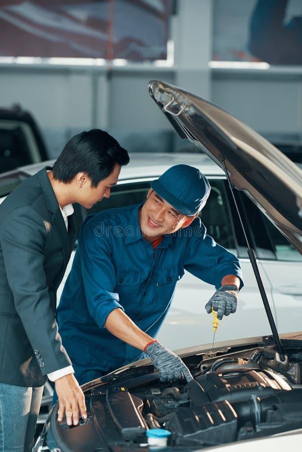 Właściciel samochodu i mechanik przy warsztatem fotografia royalty free