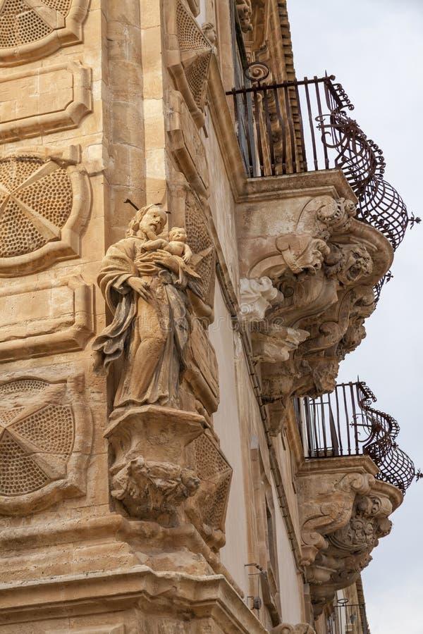 Włochy, Sicily, Scicli Ragusa prowincja, ornamentacyjne statuy Barokowy Beneventano pałac W kącie postać święty obrazy stock