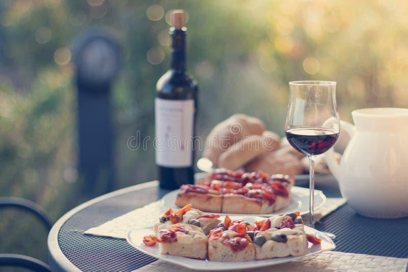 Włoski gość restauracji: Czerwone wino, świeża smakowita pizza w wieczór, wakacje obraz stock